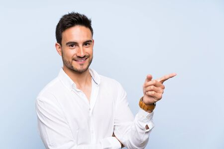 Handsome young man over isolated blue background pointing finger to the side