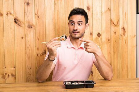 Handsome young man in a kitchen with sushi Stock Photo