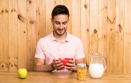 Handsome young man in a kitchen having breakfast Stock Photo