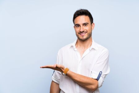 Handsome young man over isolated blue background presenting an idea while looking smiling towards