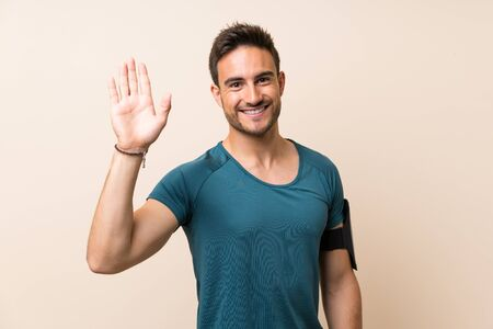Handsome sport man over isolated background saluting with hand with happy expression Stockfoto