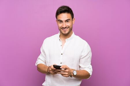 Handsome young man over isolated background sending a message with the mobile