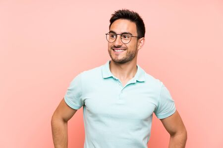 Handsome young man over isolated background with glasses and smiling