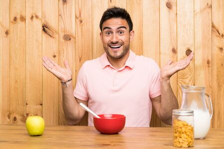 Handsome young man in a kitchen having breakfast with shocked facial expression