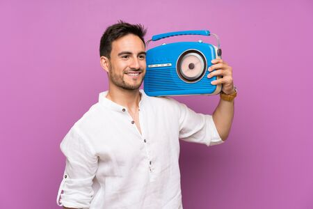 Handsome young man over purple background holding a radio