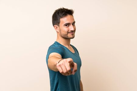 Handsome sport man over isolated background points finger at you with a confident expression Stockfoto
