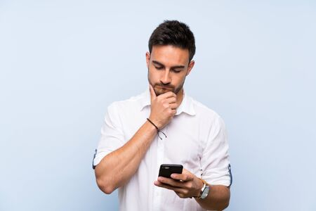 Handsome young man over isolated blue background thinking and sending a message Stok Fotoğraf