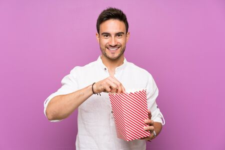 Handsome young man over purple background holding popcorns Stockfoto