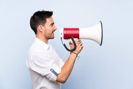 Handsome young man over isolated blue background shouting through a megaphone