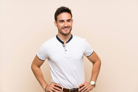 Handsome young man over isolated background posing with arms at hip and smiling Stockfoto