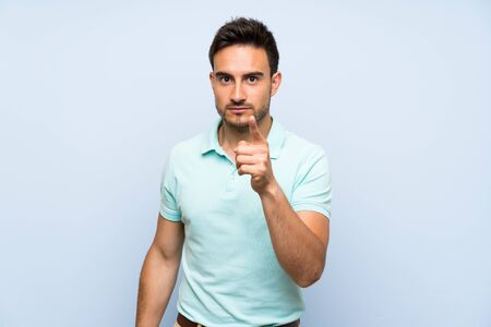 Handsome young man over isolated background frustrated and pointing to the front