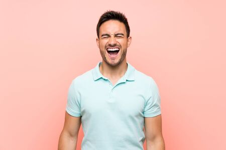 Handsome young man over isolated background shouting to the front with mouth wide open