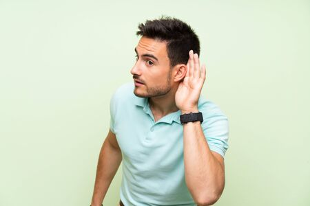Handsome young man over isolated background listening to something by putting hand on the ear Imagens