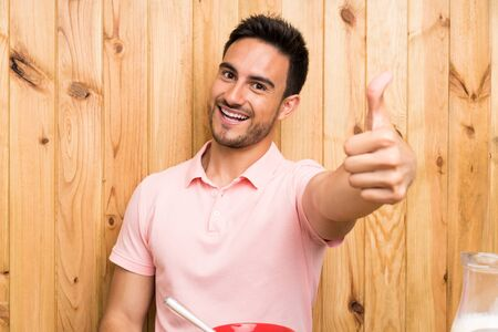 Handsome young man in a kitchen having breakfast with thumbs up because something good has happened Stockfoto