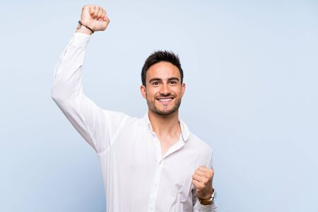 Handsome young man over isolated blue background celebrating a victory Stockfoto