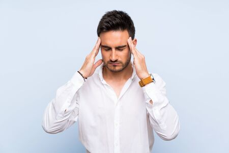Handsome young man over isolated blue background with headache