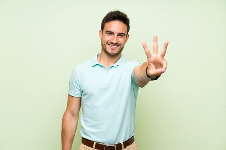 Handsome young man over isolated background happy and counting three with fingers