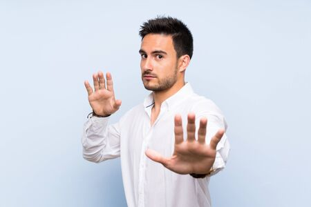 Handsome young man over isolated blue background nervous stretching hands to the front 스톡 콘텐츠