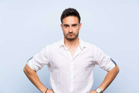 Handsome young man over isolated blue background angry