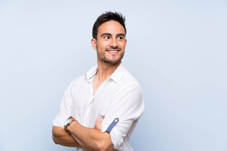 Handsome young man over isolated blue background with arms crossed and happy