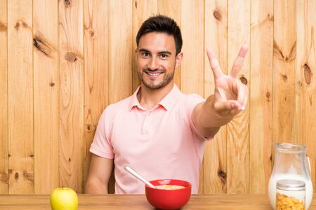 Handsome young man in a kitchen having breakfast smiling and showing victory sign Stockfoto