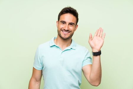 Handsome young man over isolated background saluting with hand with happy expression Stockfoto