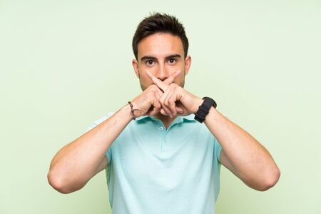 Handsome young man over isolated background showing a sign of silence gesture