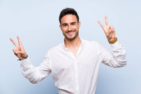 Handsome young man over isolated blue background showing victory sign with both hands Stockfoto