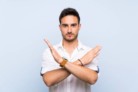 Handsome young man over isolated blue background making NO gesture