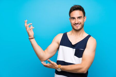 Handsome young man over isolated background extending hands to the side for inviting to come