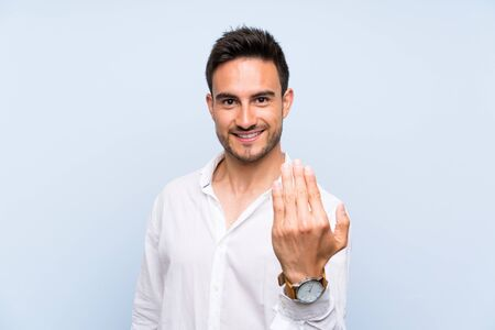 Handsome young man over isolated blue background inviting to come with hand. Happy that you came