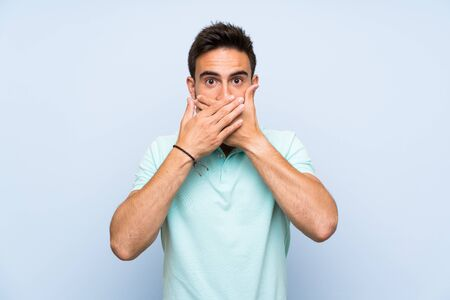 Handsome young man over isolated background covering mouth with hands