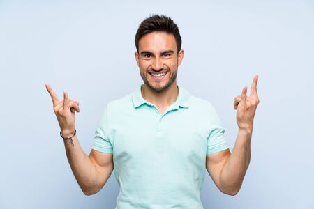 Handsome young man over isolated background making rock gesture