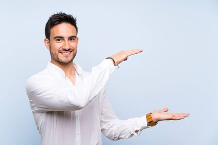 Handsome young man over isolated blue background holding copyspace to insert an ad