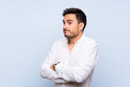 Handsome young man over isolated blue background making doubts gesture while lifting the shoulders