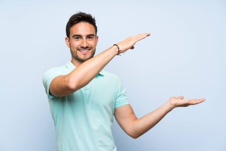 Handsome young man over isolated background holding copyspace to insert an ad