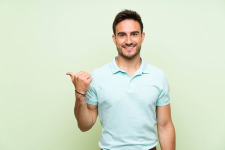 Handsome young man over isolated background pointing to the side to present a product