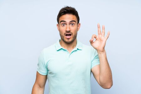 Handsome young man over isolated background surprised and showing ok sign Stockfoto