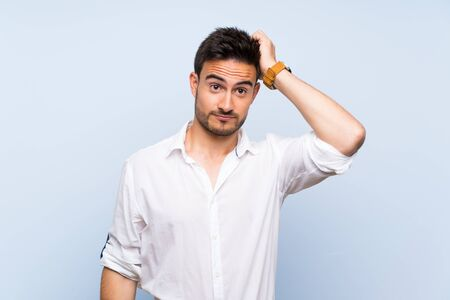 Handsome young man over isolated blue background with an expression of frustration and not understanding