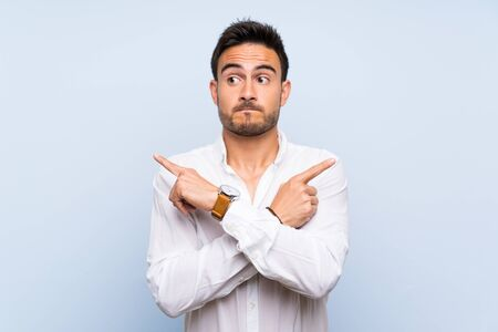 Handsome young man over isolated blue background pointing to the laterals having doubts Standard-Bild