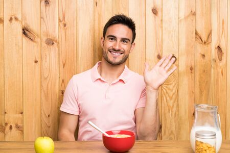 Handsome young man in a kitchen having breakfast saluting with hand with happy expression