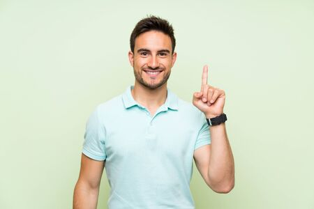 Handsome young man over isolated background showing and lifting a finger in sign of the best