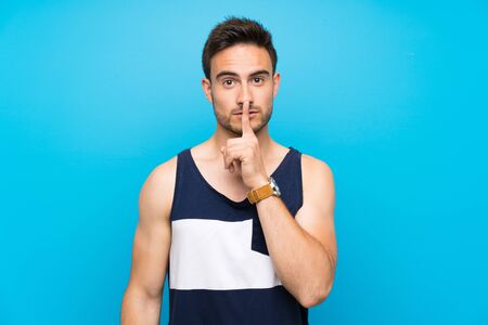 Handsome young man over isolated background showing a sign of silence gesture putting finger in mouth