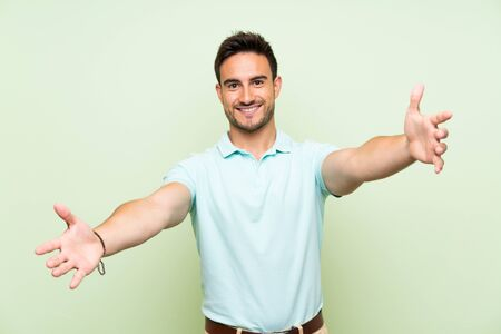 Handsome young man over isolated background presenting and inviting to come with hand Banco de Imagens