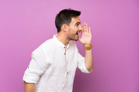 Handsome young man over isolated background shouting with mouth wide open to the lateral
