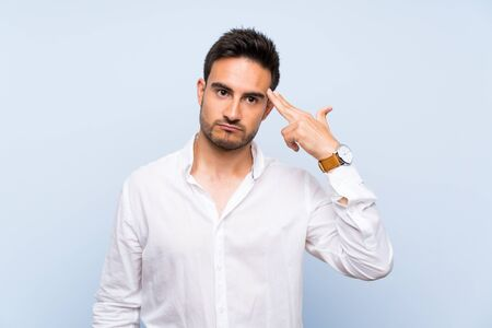 Handsome young man over isolated blue background with problems making suicide gesture 스톡 콘텐츠