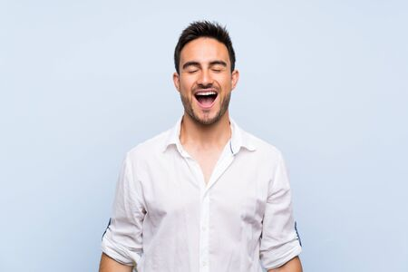Handsome young man over isolated blue background shouting to the front with mouth wide open