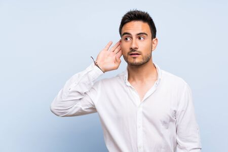 Handsome young man over isolated blue background listening to something by putting hand on the ear