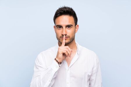 Handsome young man over isolated blue background showing a sign of silence gesture putting finger in mouth Imagens