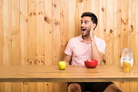 Handsome young man in a kitchen having breakfast shouting with mouth wide open